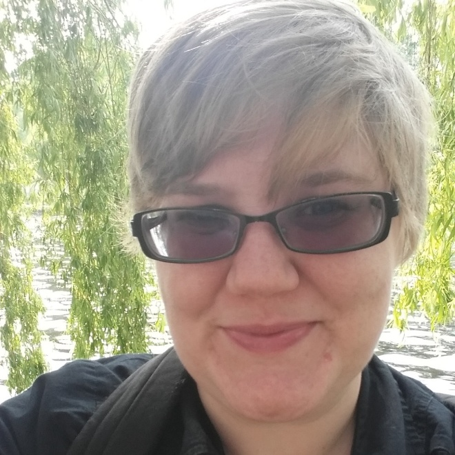 A selfie of the author, taken standing under a weeping willow tree by the river Spree. The sun is shining off the water and in her hair.